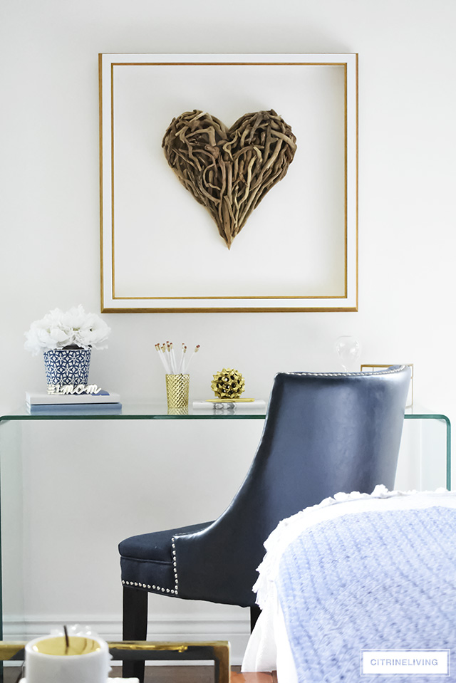 Beautiful writing desk area in this Boho-Glam bedroom featuring driftwood heart artwork paired with a modern waterfall glass desk. Layers of pattern and texture throughout the space add an eclectic, collected vibe.