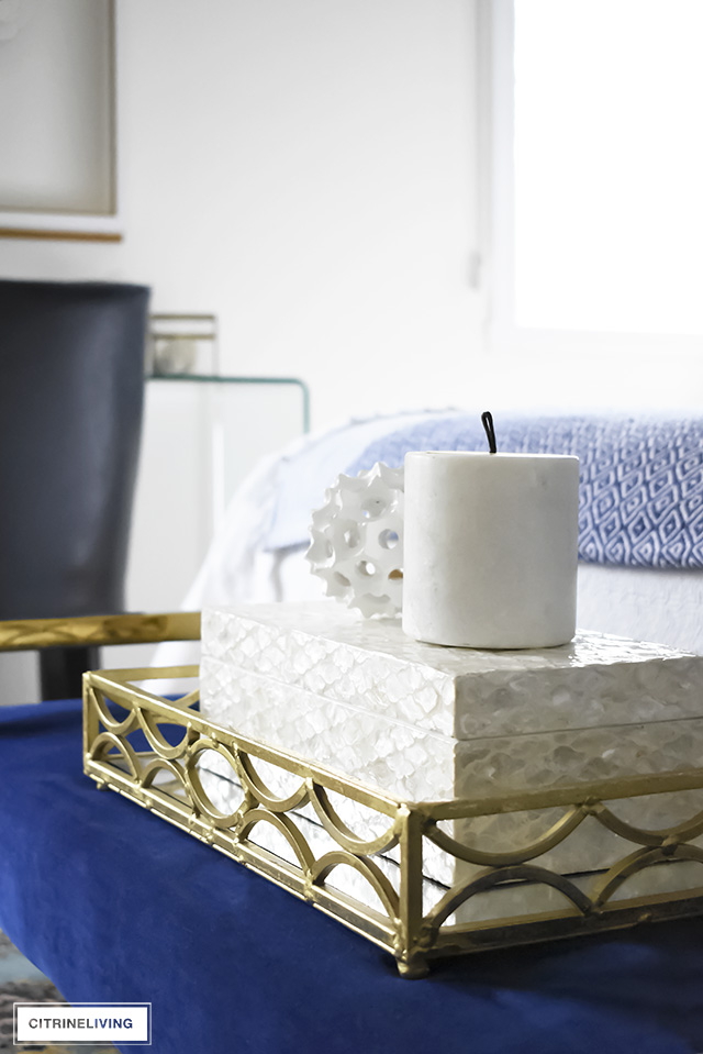 A beautiful blue velvet bench with brass tray and layers of white and cream accessories.