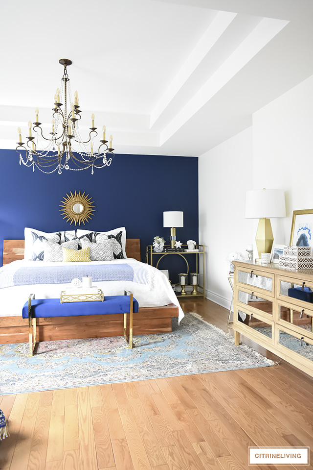 A gorgeous Boho-Glam bedroom makeover with the perfect blend of old and new - a modern bed, vintage rug, crystal chandelier tied together with eclectic accessories and brass elements throughout.