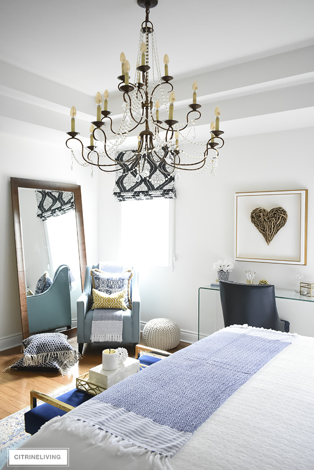 A gorgeous reading nook with layers of blues - vintage rug, eclectic pillows, graphic roman blind are layered together create the perfect boho-glam bedroom.
