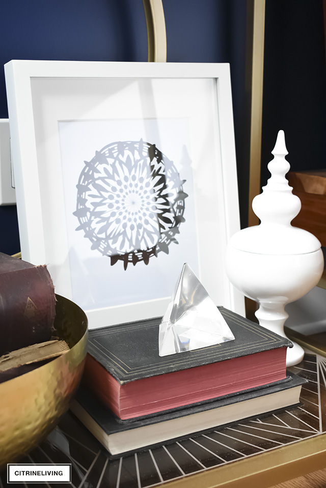 An eclectic mix of accessories layered together adds interest to your nightstand or shelves. Medallion artwork, vintage books and sculptural accessories with touches of brass are a chic mix!