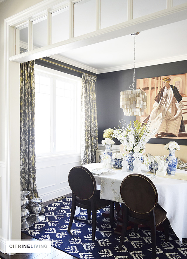Dining room with pattern on pattern textiles, black walls.