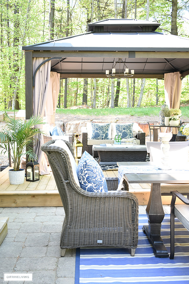 Outdoor patio with gazebo, dining table and wingback chairs.