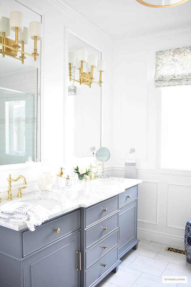 Favorite Makeovers! Master bathroom makeover with grey vanity, marble counters, brass lighting and accents. Blue and white garden stool.