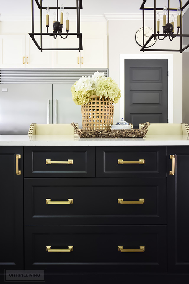 Black kitchen island with brass hardware pulls and quartz counters.