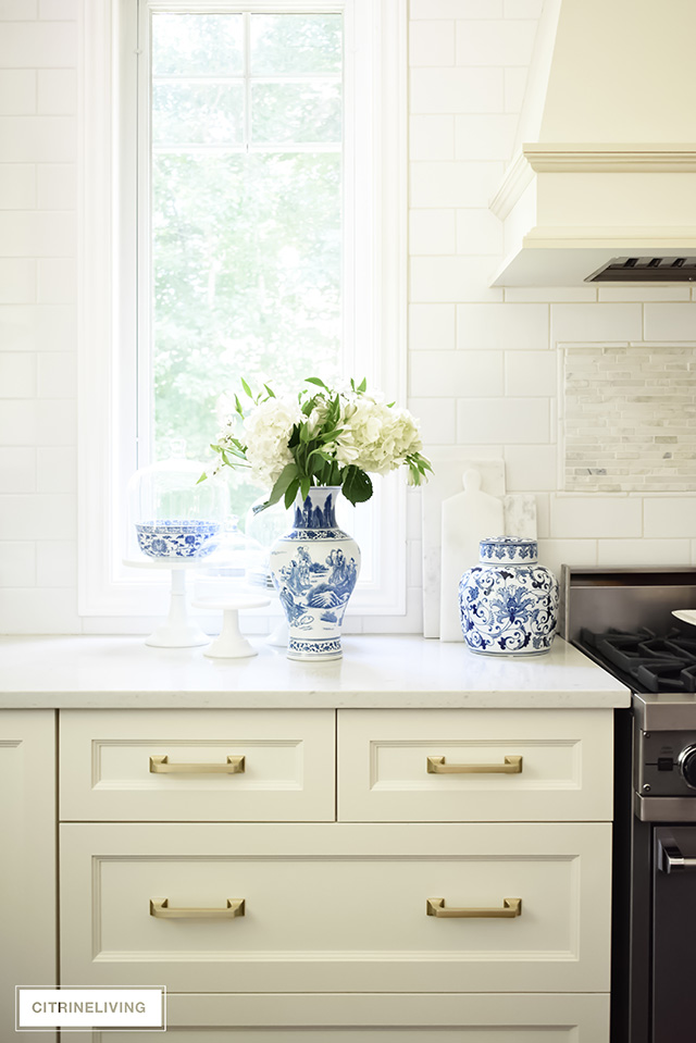 Ivory kitchen cabinets, brass hardware drawers pulls. Blue and white vase with flowers.