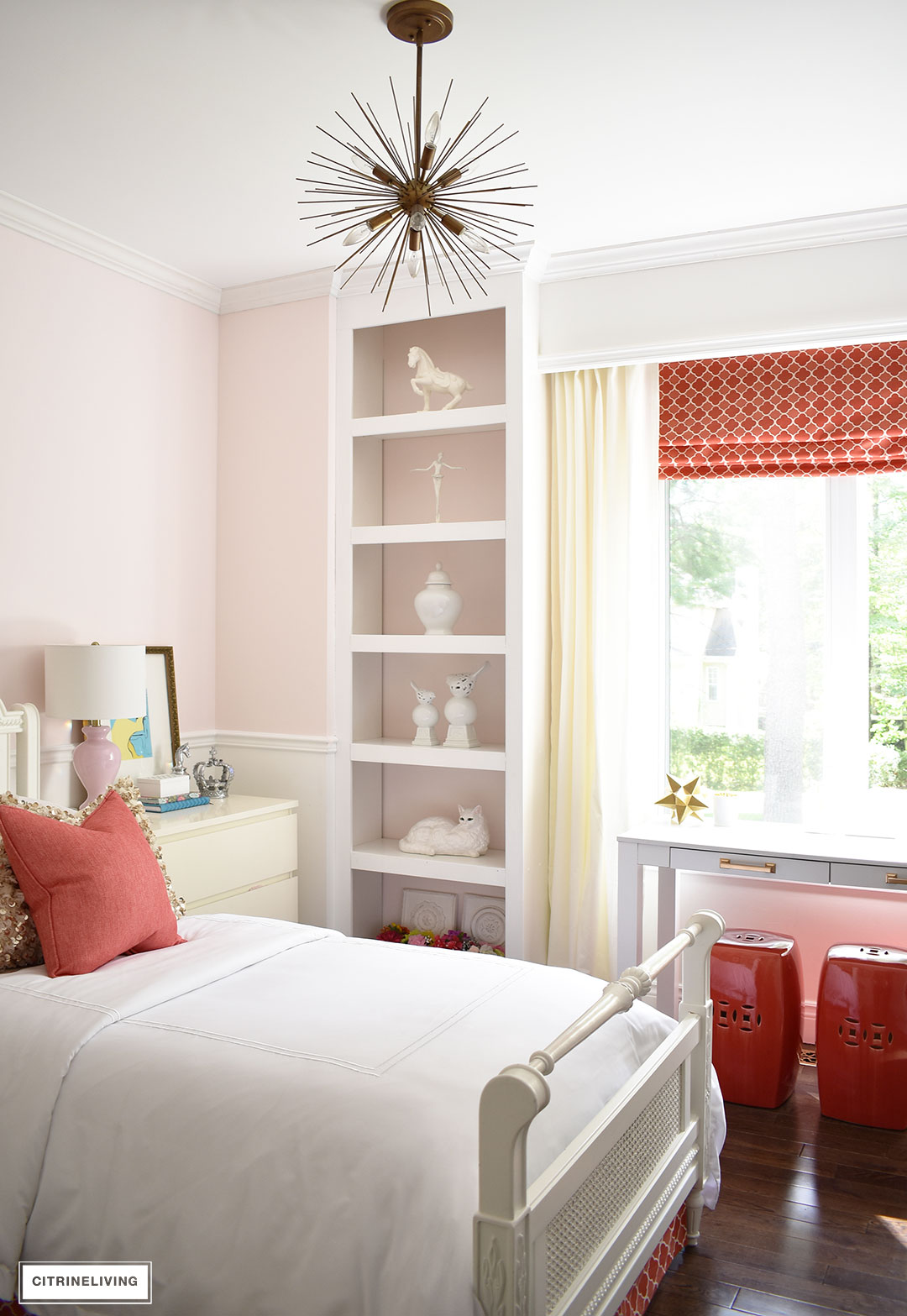 Girl's bedroom with blush pink walls, white trim, brass and coral accents.