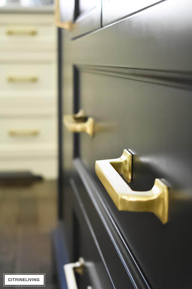 Brass hardware pulls on black kitchen island drawers.