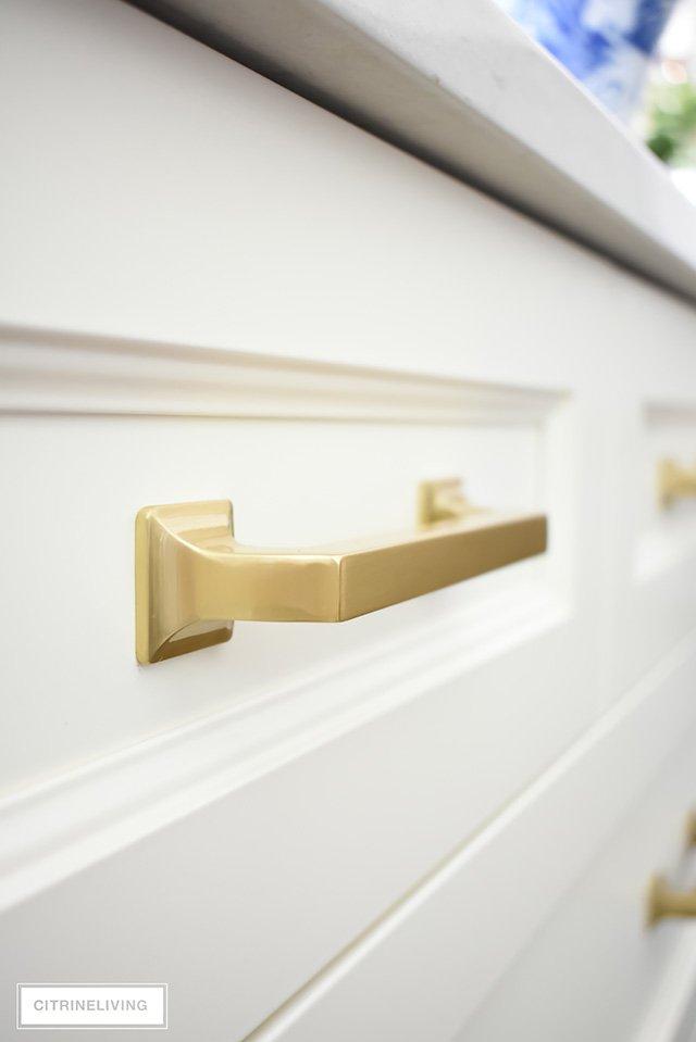 Brass hardware pulls on ivory kitchen drawers.