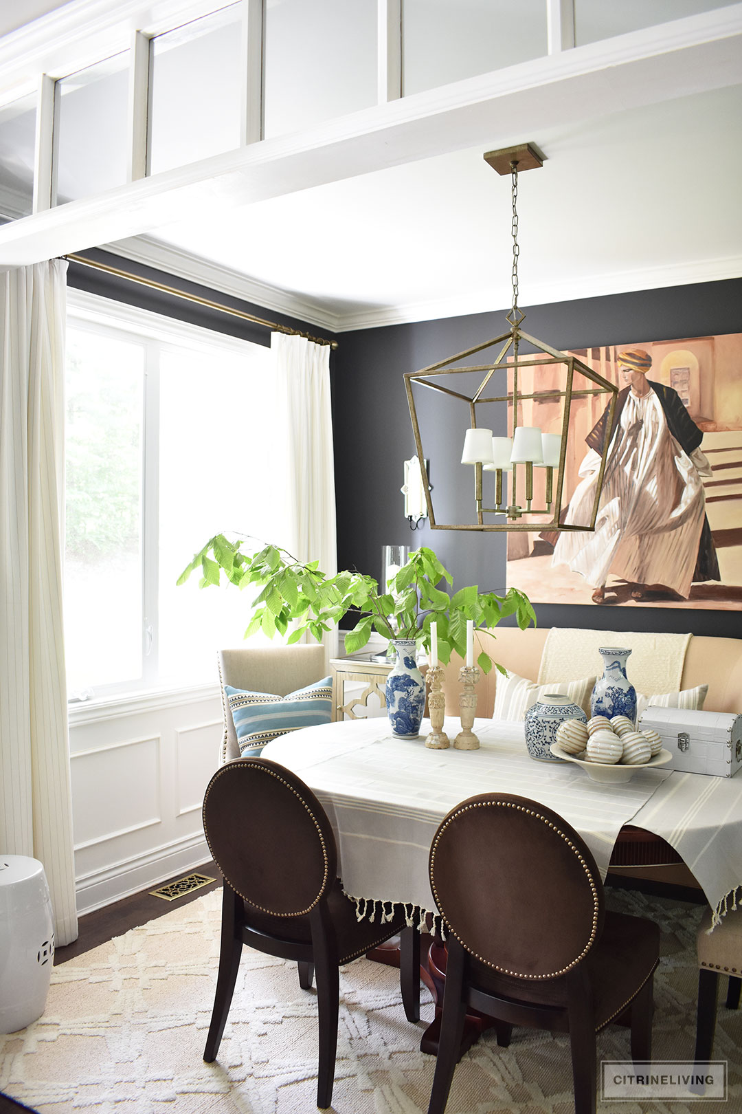 Dining room with black walls, white drapes, transoms.