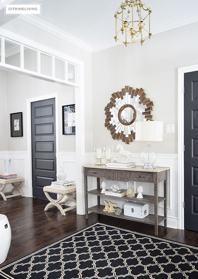 Entryway with black and white rug, wooden console table and sunburst mirror.