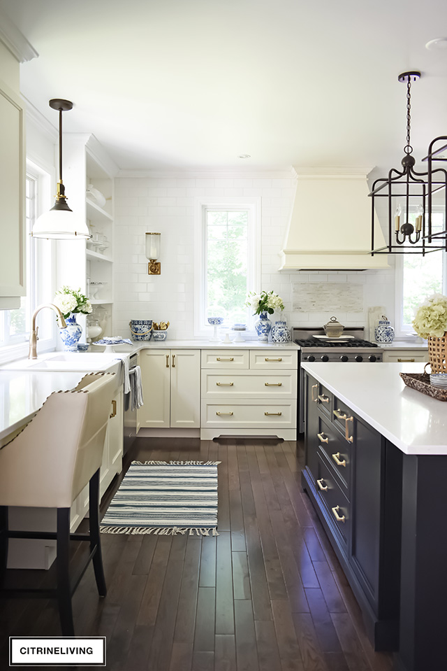 Traditional kitchen with ivory perimeter cabinets, black island with brass hardware, and counter to ceiling subway tile wall.