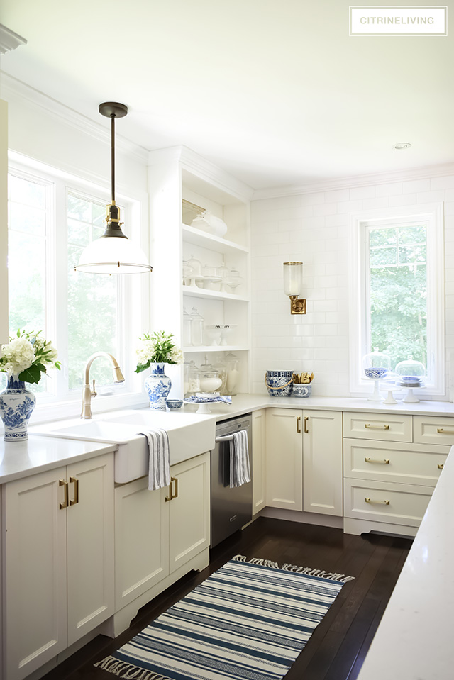 White farm sink with industrial pendant light and brass faucet. Kitchen styling ideas.