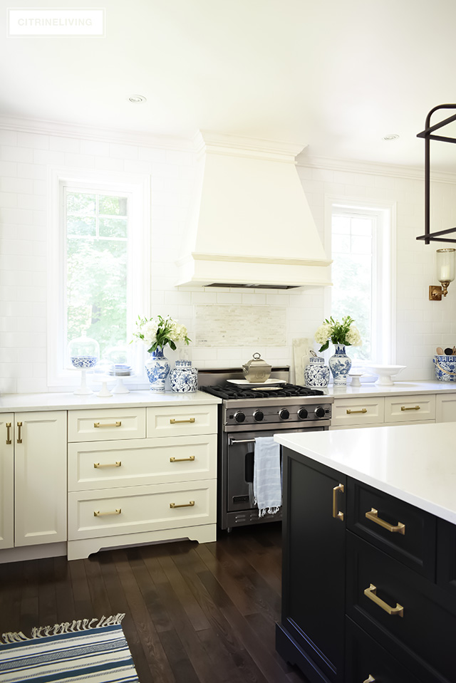 Kitchen with custom range hood, white subway tile wall, no upper cabinets and brass hardware pulls.
