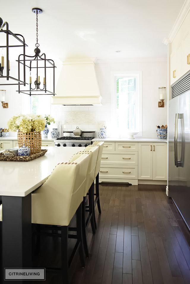 Kitchen stools with brass nailhead trim at large island with pendant lighting.