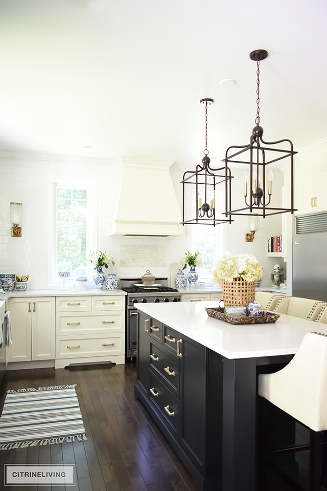 Traditional kitchen with back island, ivory perimeter cabinets and brass hardware.