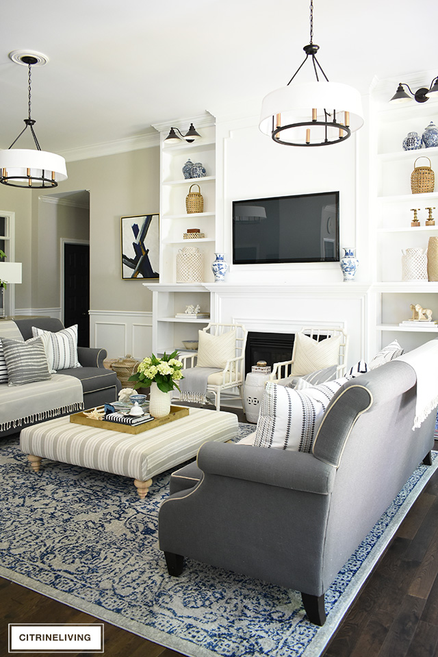 Living room with large builtin bookshelves, grey sofas, double chandeliers, blue vintage rug.