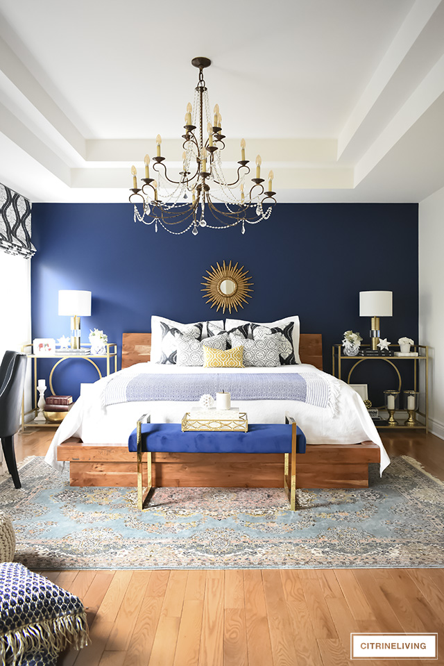 Favorite Makeovers! Master bedroom makeover with blue accent wall, vintage rug and chandler and brass accents.