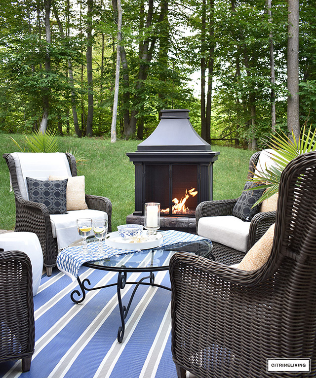 Outdoor patio conversation zone with fireplace and wingback chairs.