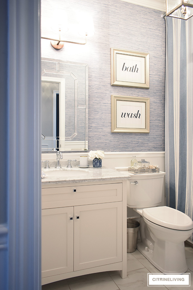 Favorite Makeovers! Coastal inspired bathroom with blue grasscloth wallpaper and white vanity with grey marble counters.