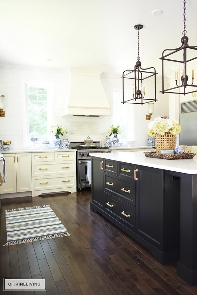 Ivory kitchen with contrasting black island and brass hardware. Large scale pendant lighting over the island.