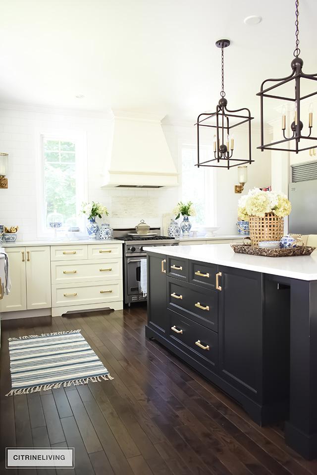 White kitchen with black island, pendant lighting over island, oak hardwood floors.
