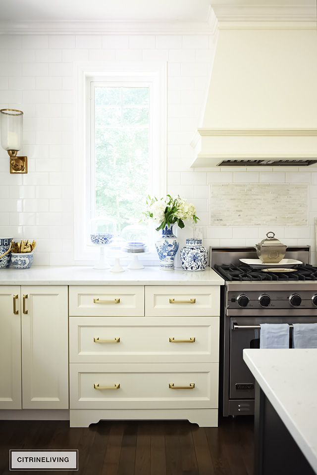 Ivory kitchen cabinets, brass hardware drawers pulls. Blue and white vase with hydrangeas.