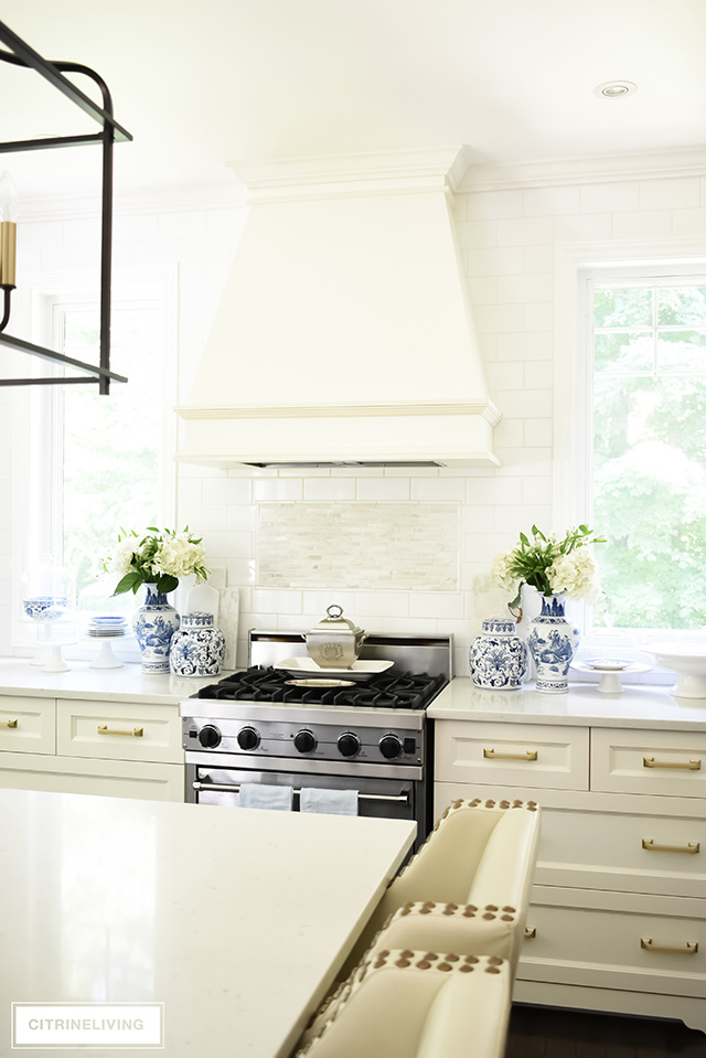 White kitchen with subway tile wall and no upper cabinets.