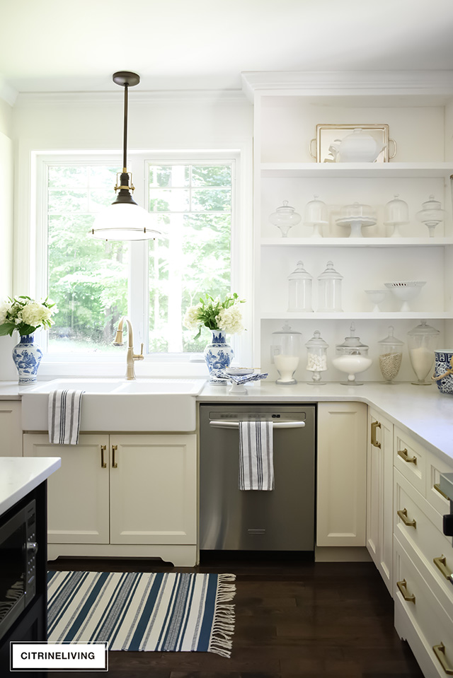 White kitchen with brass hardware pulls, white farm sink, brass faucet and open shelving.