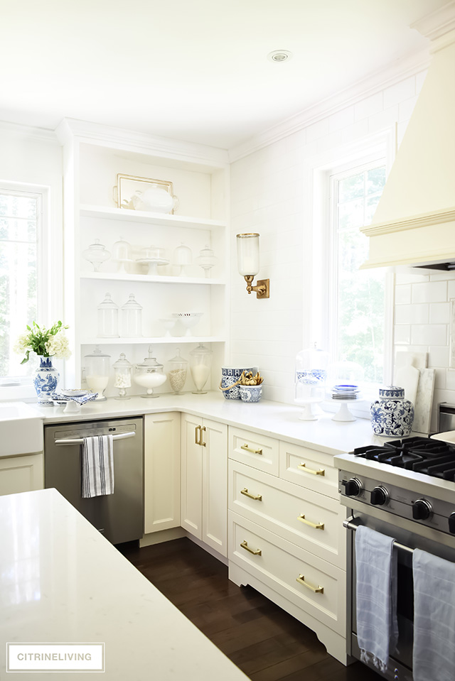 White kitchen styling ideas for builtin open shelving, drawers with brass hardware pulls.
