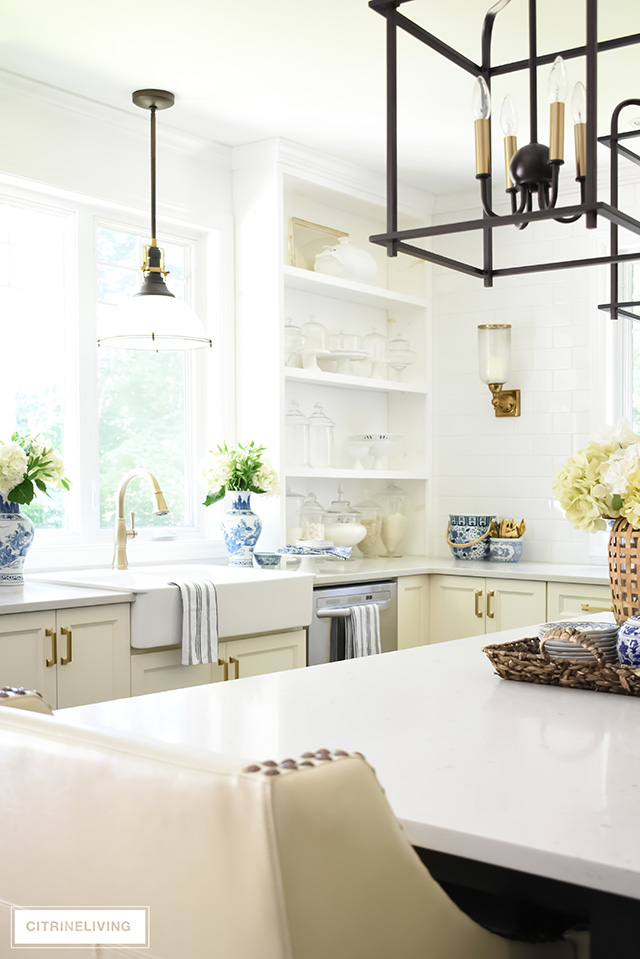 White kitchen with farm sink, industrial pendant light and brass faucet.