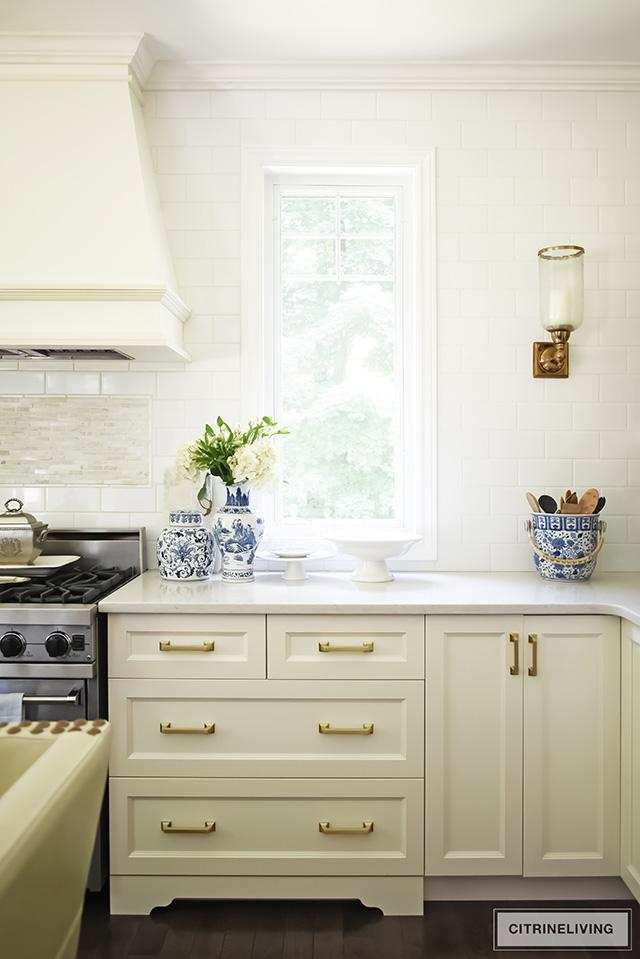 White kitchen with brass hardware pulls.