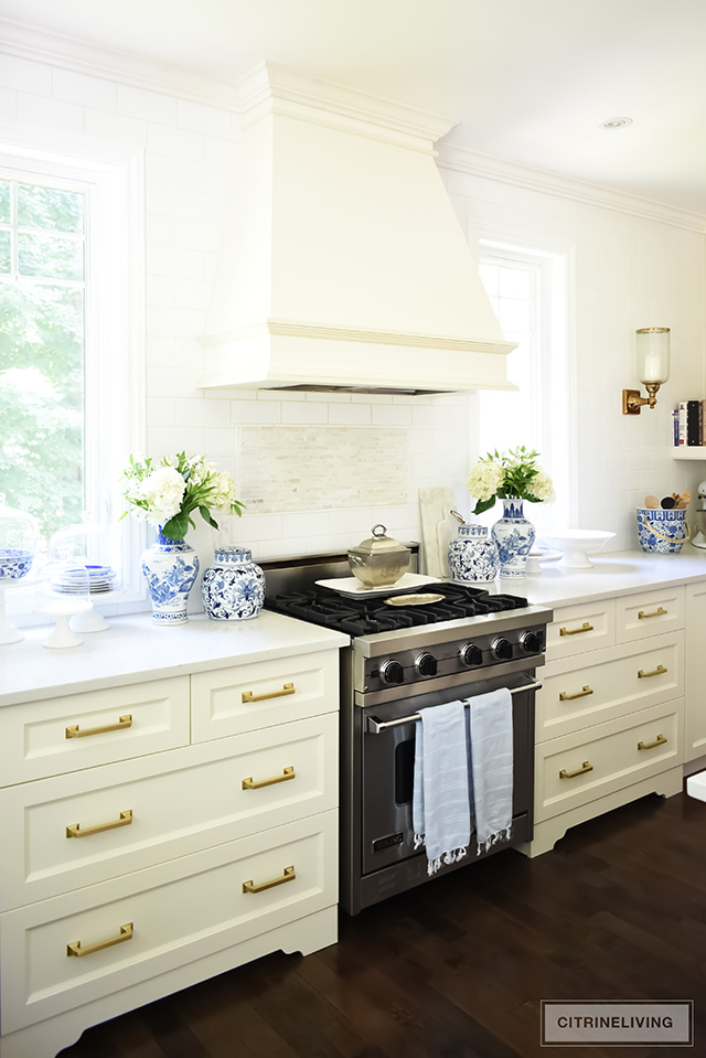 White kitchen with drawers flanking the stove and brass hardware pulls.