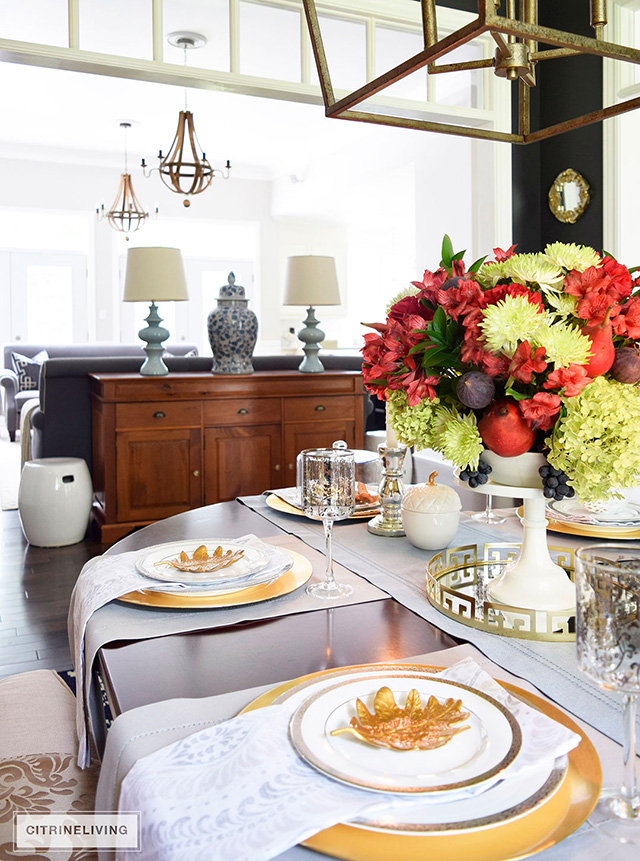 Fall tablescape with gold dishware and floral arrangement with fresh fruit.