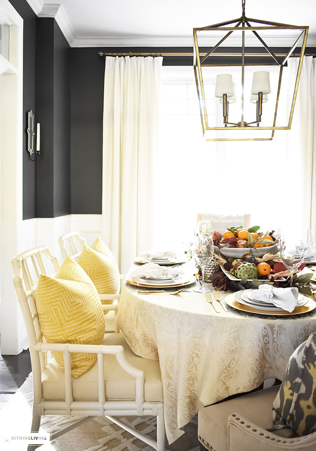 Fall tablescape in modern dining room with black walls, and large lantern chandelier.