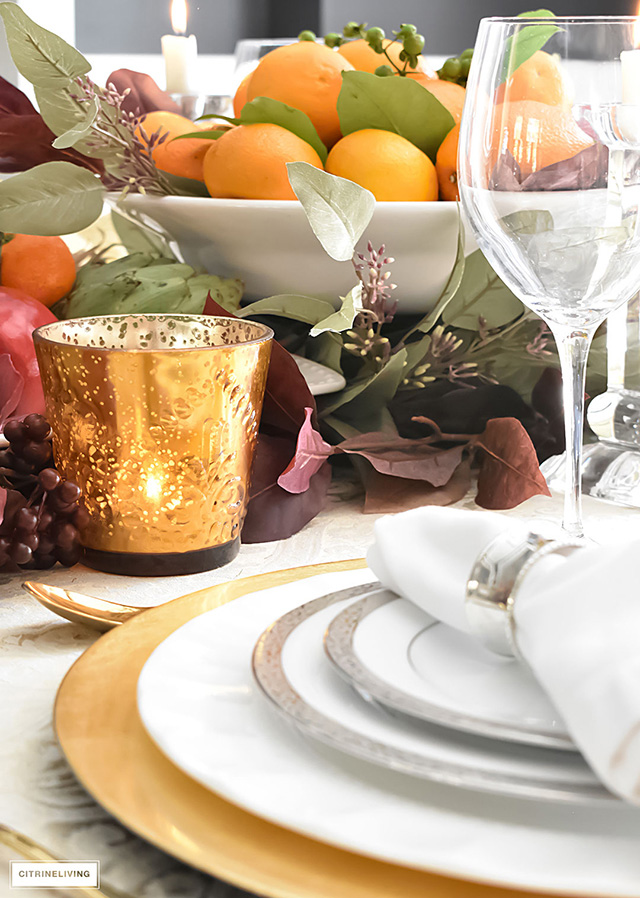 Fall tablescape using gold dishware, fresh oranges as centrepiece and faux foliage.