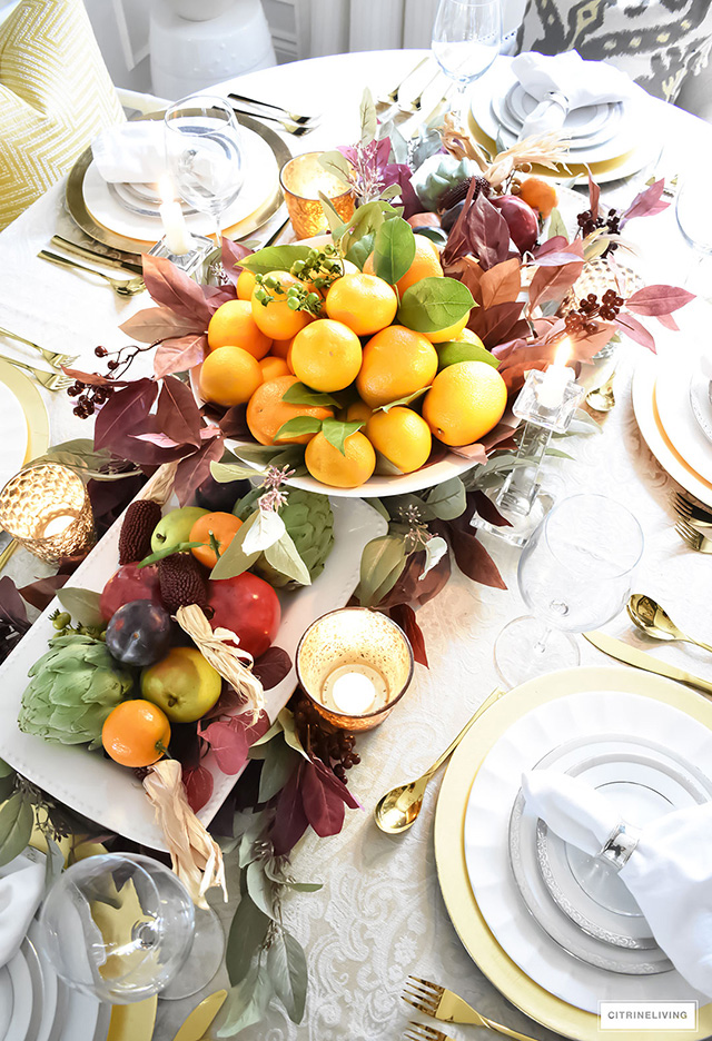 Gorgeous fall tablescpae with fresh fruit centrepiece and rich fall colors.