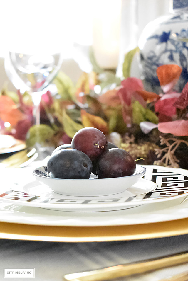 Fresh plums adorn a fall place setting.