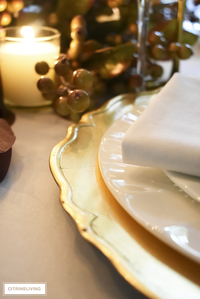 A white and gold Thanksgiving tablescape, with beautiful fall foliage in warm, earthy tones is a simple and elegant way to entertain for the holidays!
