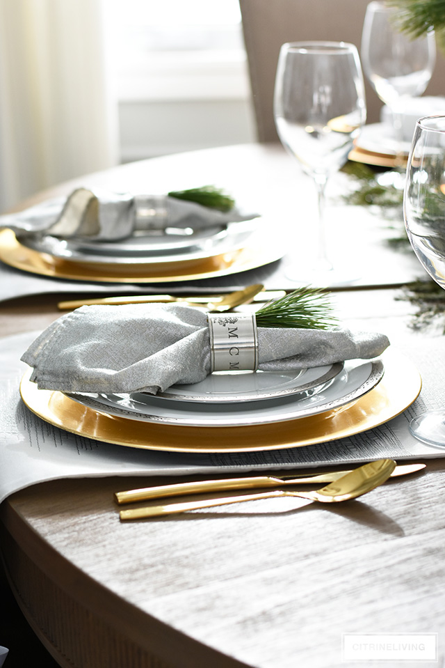 Beautiful Christmas tablescape with fresh greenery, silver and gold china and antique silver napkin rings.