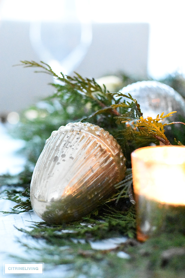 Christmas table with fresh greenery and beautiful ornaments - mercury glass acorn and votive candle.