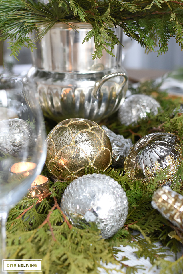 A Christmas table with fresh greenery and beautiful ornaments is easier to create than you think! It's simple, sophisticated, elegant and oh, so festive!