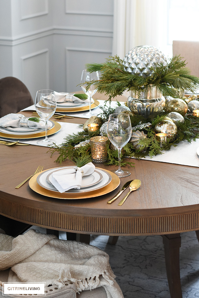 Gorgeous Christmas table with fresh greenery and beautiful metallic ornaments, gold and silver china and flatware.