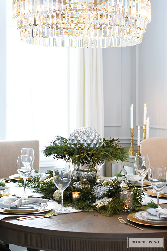 Create a stunning Christmas table with fresh greenery, beautiful ornaments and an elegant silver champagne bucket.