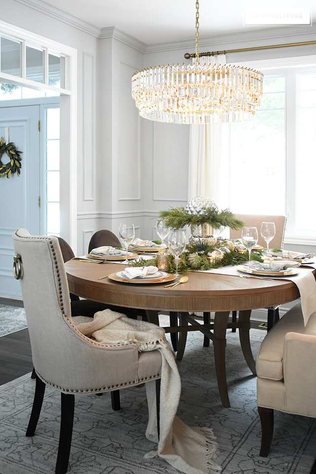 Christmas table with fresh greenery is perfect for holiday entertaining in this gorgeous dining room with elegant crystal chandelier, wall panelling and casual, relaxed furniture.