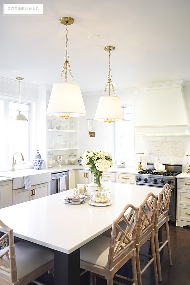 Kitchen pendant lighting with shades and chippendale barstools add chic sophistication to this space.