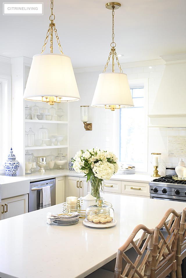 Tailored pendant lighting with shades and brass detailing is an elegant and chic addition in the kitchen.