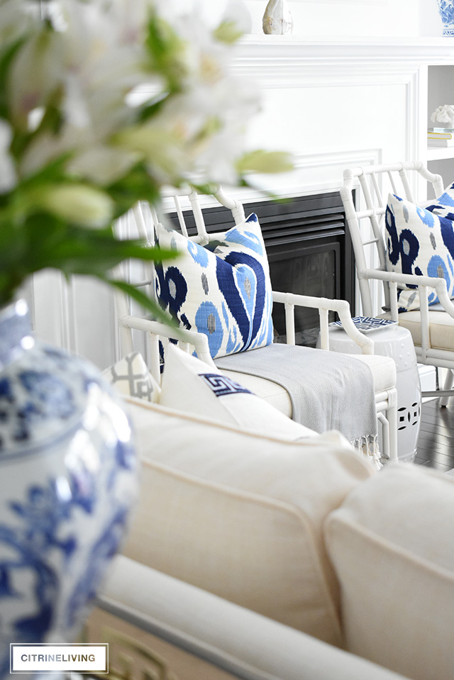 Beautiful blue ikat print pillows add graphic punch to this living room with layers of warm whites.