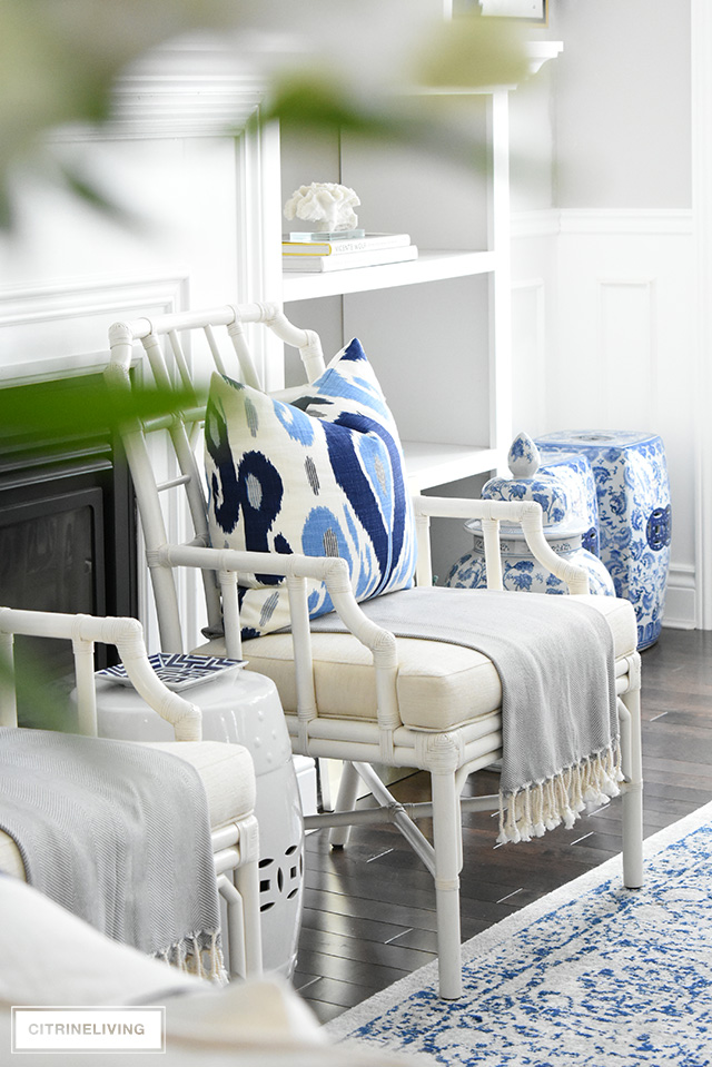Beautiful John Robshaw blue ikat print pillows add graphic punch to this living room with layers of warm whites.