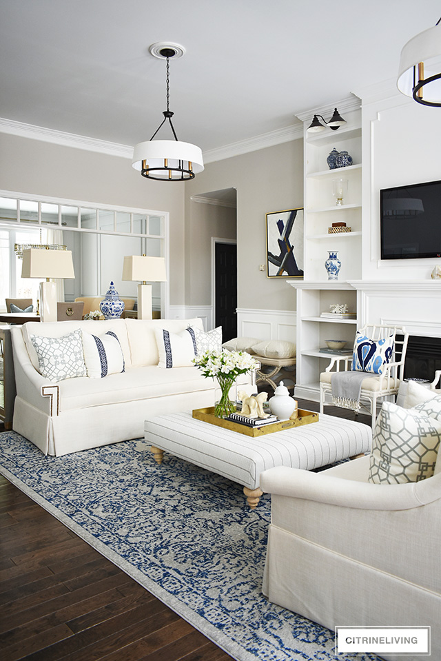 Living room reveal featuring gorgeous new white sofas, cream lamps, designer pillows and a recovered ottoman - this space is elegant and sophisticated yet still casual and inviting!